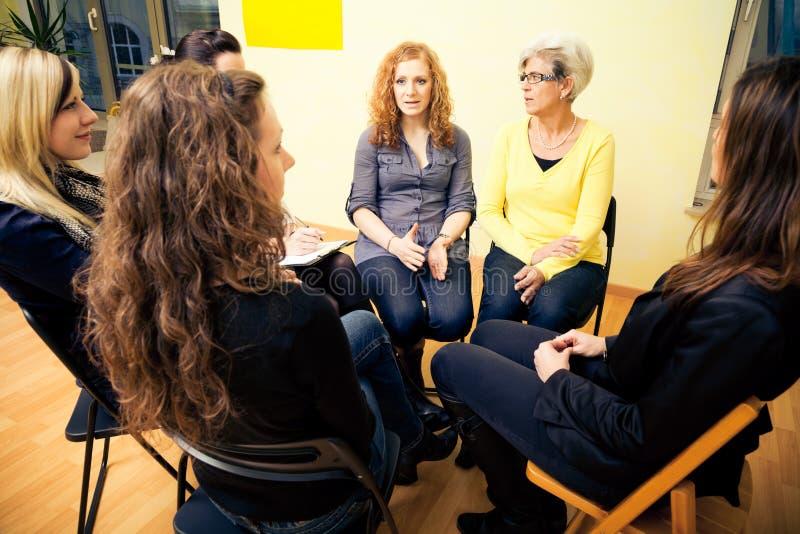 Frauengruppe, die in einem Kreis, besprechend sitzt stockbild