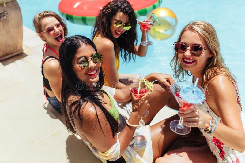 Frauengruppe, die heraus durch das Pool mit Getränken hängt lizenzfreies stockbild
