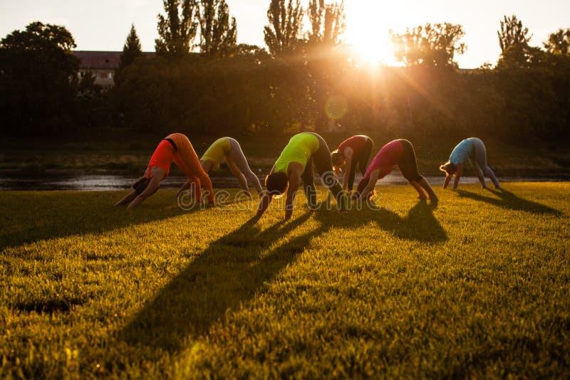 Frauengruppe, die Yoga durch den Fluss tut lizenzfreies stockfoto
