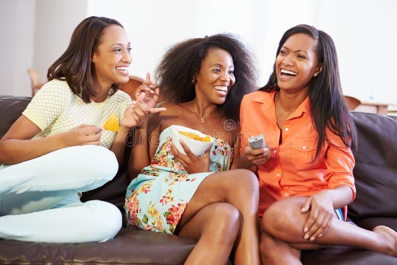 Frauengruppe, die zusammen im Sofa Watching Fernsehen sitzt lizenzfreie stockbilder
