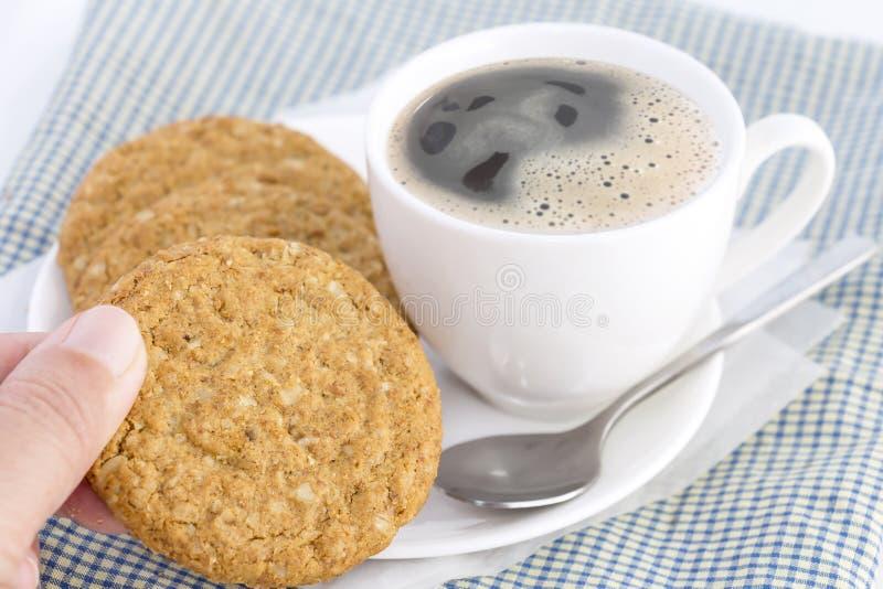 Frauenhände, die selbst gemachte Keksplätzchen gemacht vom Hafermehl gestapelt in der Platte mit heißer Kaffeetasse auf Stoff auf lizenzfreie stockfotos