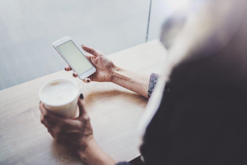 Frauenhändchenhalten Smartphone und simsende Mitteilung Weibliche Hände unter Verwendung des Handys Nahaufnahme auf unscharfem Hi stockbilder