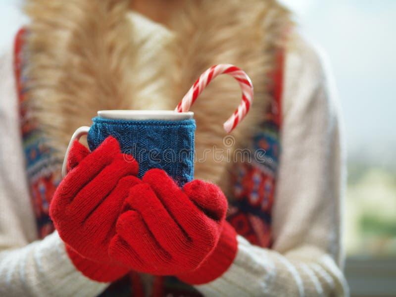 Frauenhände in den woolen roten Handschuhen, die einen gemütlichen Becher mit heißem Kakao, Tee oder Kaffee und eine Zuckerstange lizenzfreie stockbilder