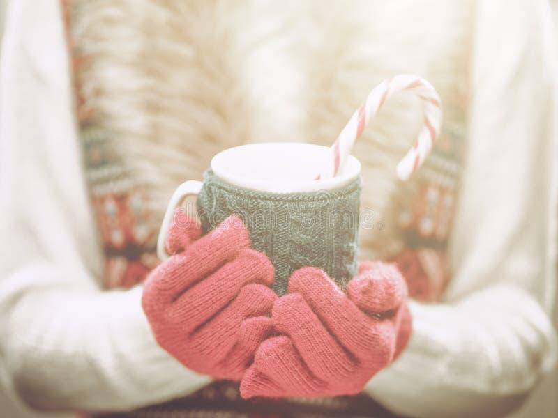Frauenhände in den woolen roten Handschuhen, die einen gemütlichen Becher mit heißem Kakao, Tee oder Kaffee und eine Zuckerstange lizenzfreies stockbild