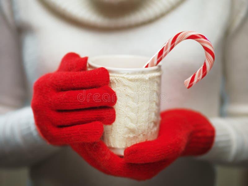 Frauenhände in den woolen roten Handschuhen, die gemütlichen Becher mit heißem Kakao, Tee oder Kaffee und eine Zuckerstange halte stockfotografie