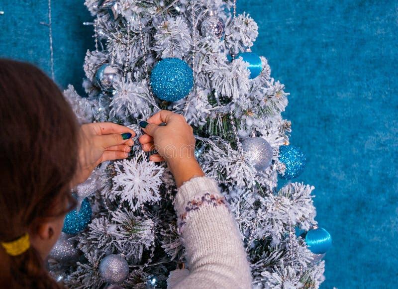 Frauenhände in der Strickjacke, die Weihnachtsbaum mit Bällen auf blauem Hintergrund verziert lizenzfreie stockfotos