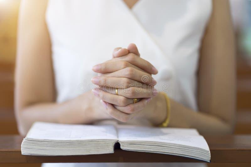 Frauenhände, die auf einer heiligen Bibel in der Kirche für Glaubenkonzept, Geistigkeit und christliche Religion beten lizenzfreie stockfotos