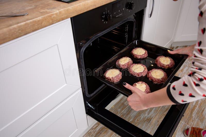 Frauenhände, die Backblech mit Koteletts oder Fleischklöschen und in Ofen setzen stockfotografie