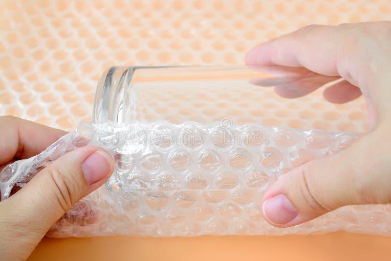 Frauenhände, die ein Glas für Wasser mit weißer transparenter Luftpolsterfolie auf einem gelben Hintergrund verpacken Material fü lizenzfreie stockfotos