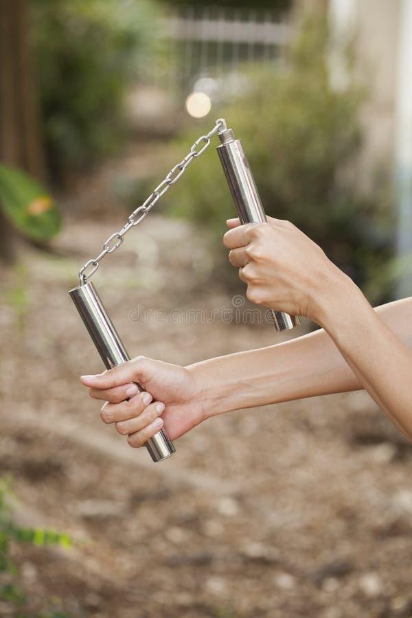 Frauenhände, die ein nunchaku halten stockfoto