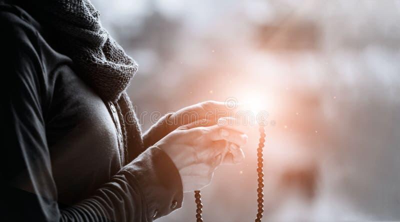 Frauenh?nde, die ein Perlenrosenbeet auf dem Beleuchten von backgrouns, black&white, Konzept des religi?sen Glaubens beten und ha stockfotos