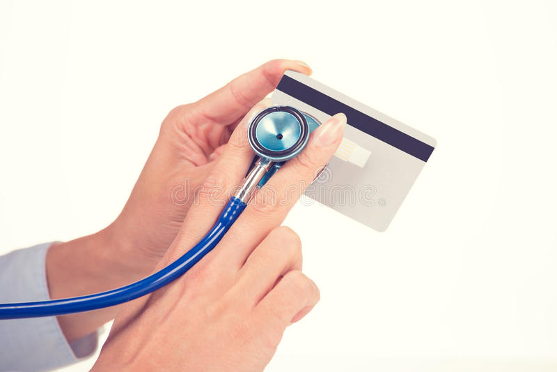 Frauenhände, die hörende Kreditkarte mit Stethoskop halten stockfotos