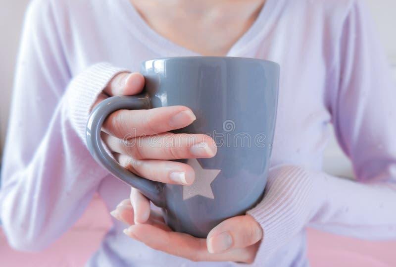 Frauenhände, die Kaffeetasse halten Mädchen im Strickjackenholdingbecher Morgengetränklebensstil lizenzfreies stockfoto