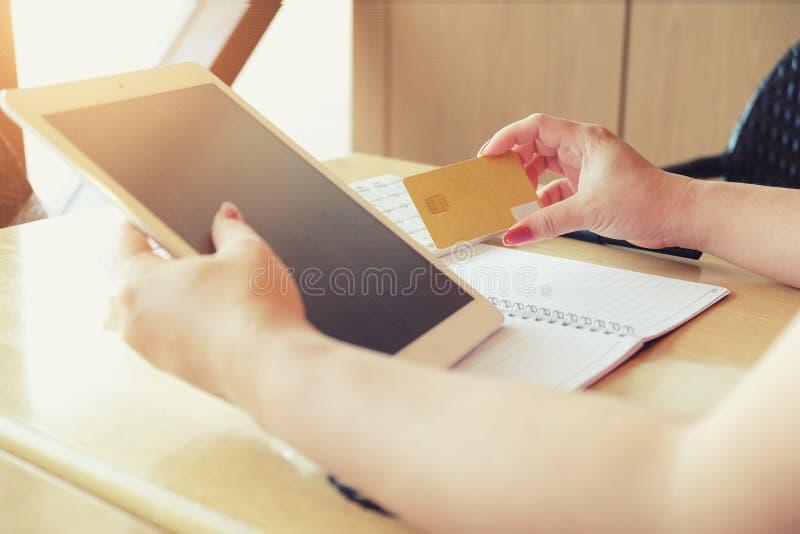 Frauenhände, die Kreditkarte halten und Laptop verwenden lizenzfreie stockfotografie