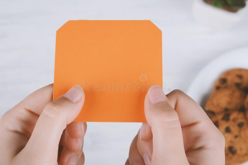 Frauenhände, die leeres orange Briefpapier halten stockbilder