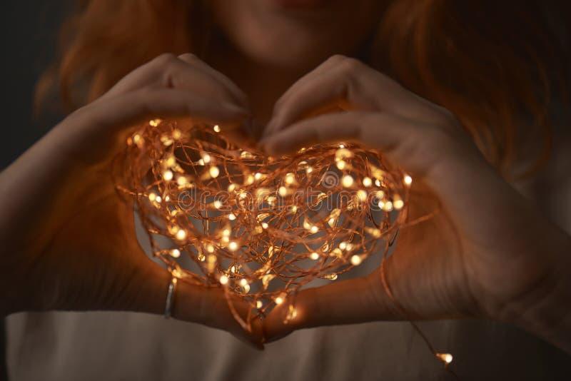 Frauenhände, die Lichterkette in der Dunkelheit halten lizenzfreie stockbilder