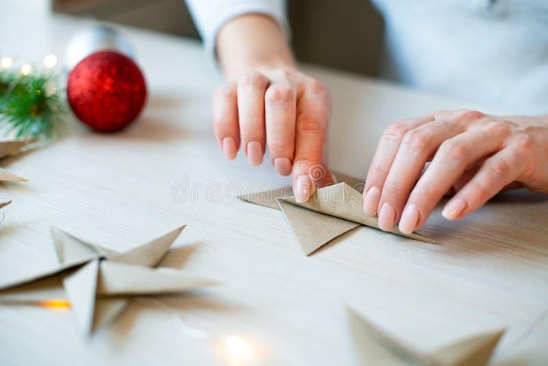 Frauenhände, die Origamipapierstern für Weihnachtsdekoration falten lizenzfreies stockbild