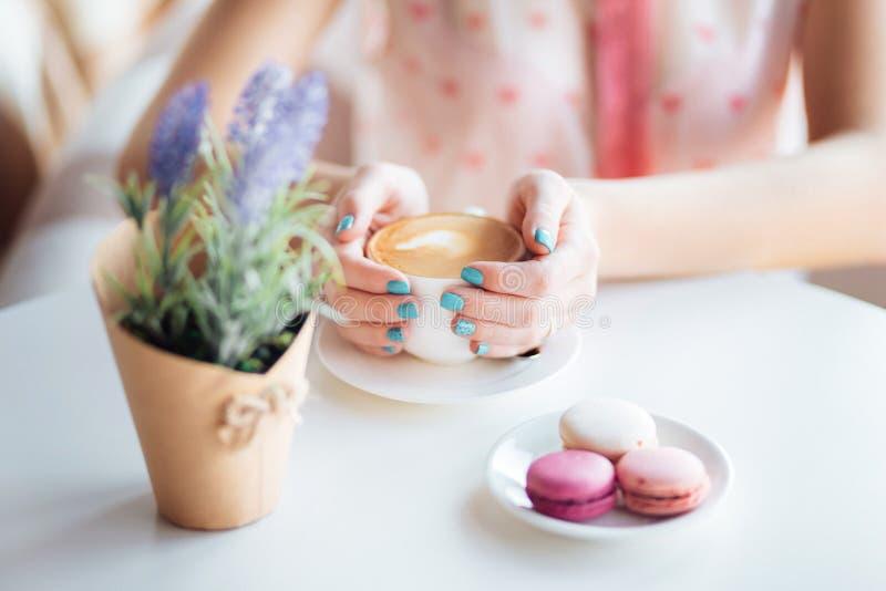 Frauenhände, die Tasse Kaffee halten Macarons auf Tabelle und Lavendel lizenzfreie stockbilder