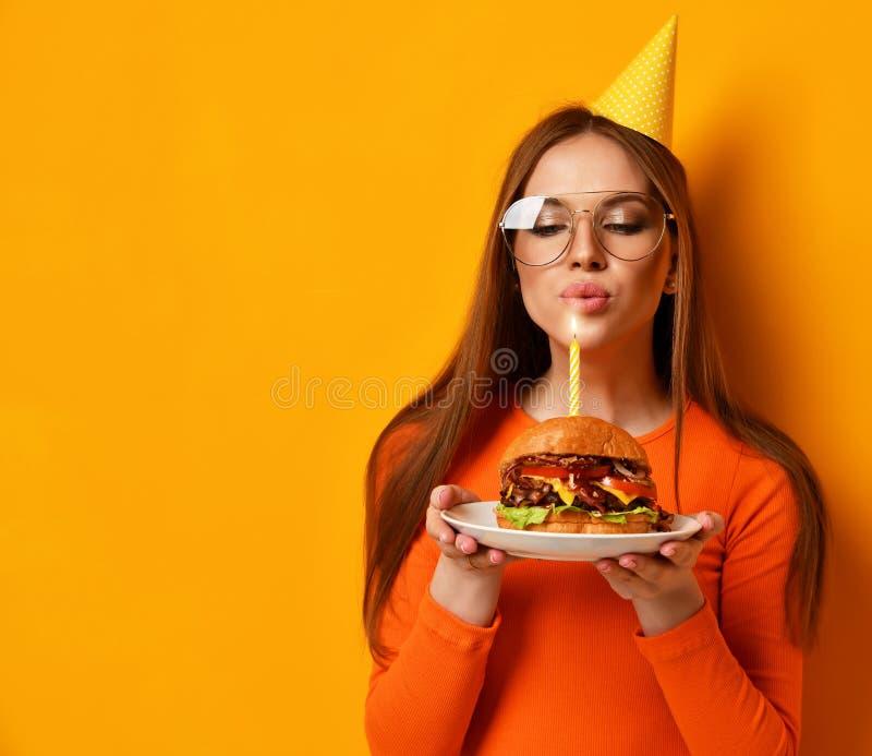 Frauenhände halten großes Burgergrillsandwich mit Rindfleisch und brennender Kerze für Geburtstagsfeier auf Gelb lizenzfreie stockfotos