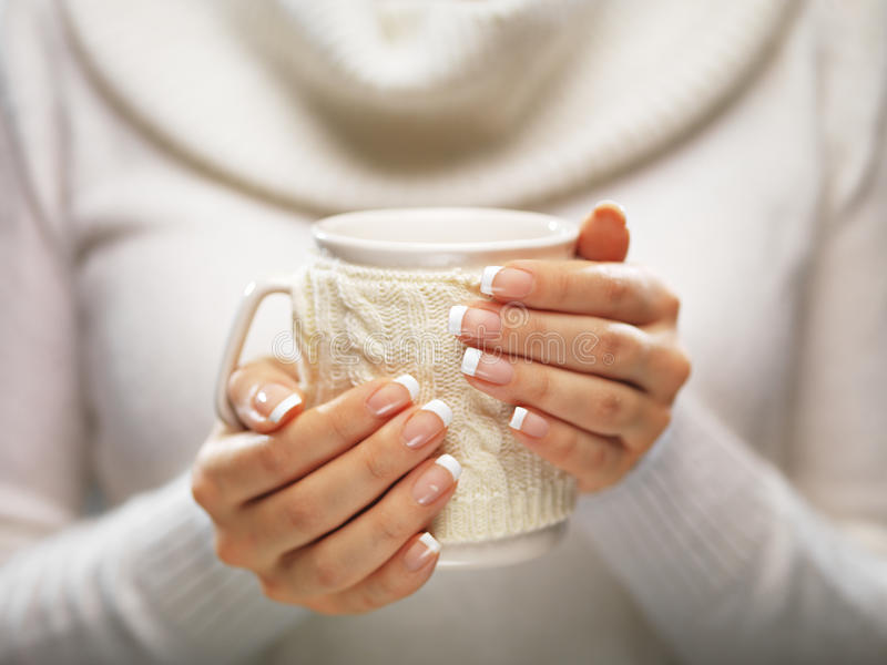 Frauenhände mit eleganten Nägeln der französischen Maniküre entwerfen das Halten eines gemütlichen gestrickten Bechers Winter- un stockbild