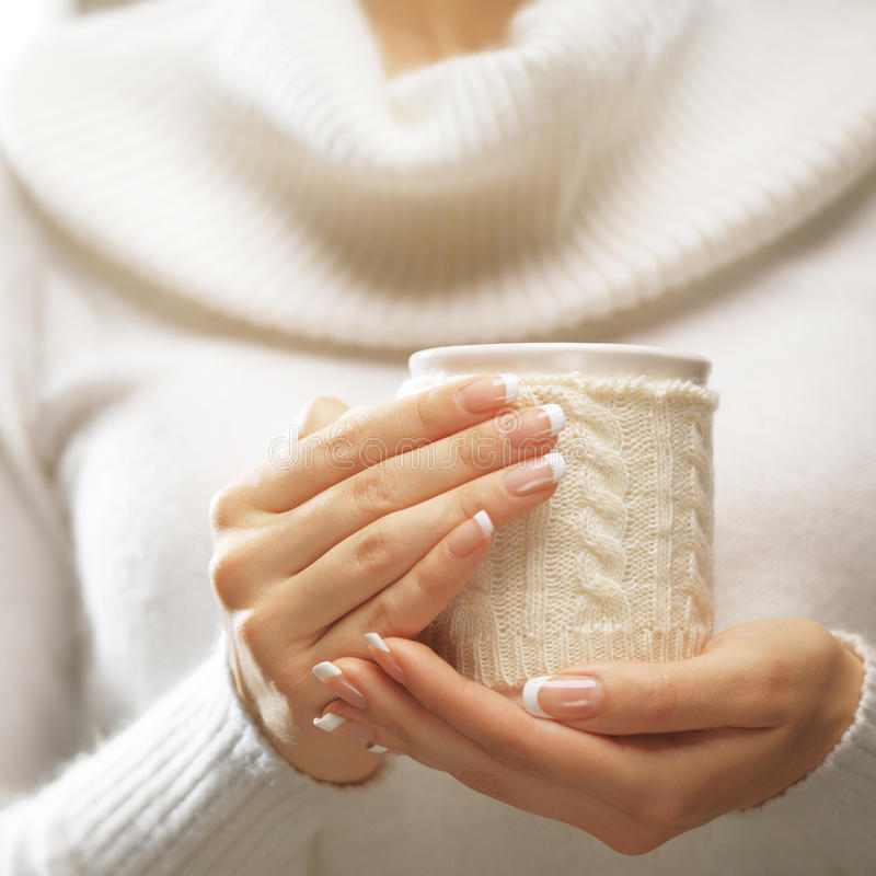 Frauenhände mit eleganten Nägeln der französischen Maniküre entwerfen das Halten eines gemütlichen gestrickten Bechers Winter- un stockfoto