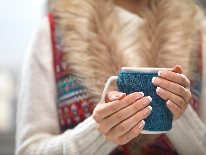 Frauenhände mit eleganten Nägeln der französischen Maniküre entwerfen das Halten eines gemütlichen gestrickten Bechers Winter- un lizenzfreies stockfoto