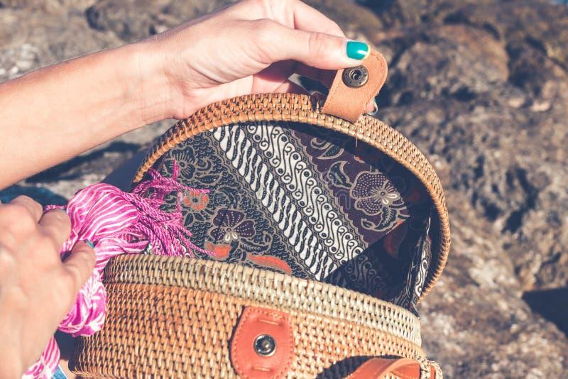 Frauenhände mit modernem stilvollem nacktem Rattan bauschen sich draußen Tropeninsel von Bali, Indonesien Rattan und Seide stockbilder