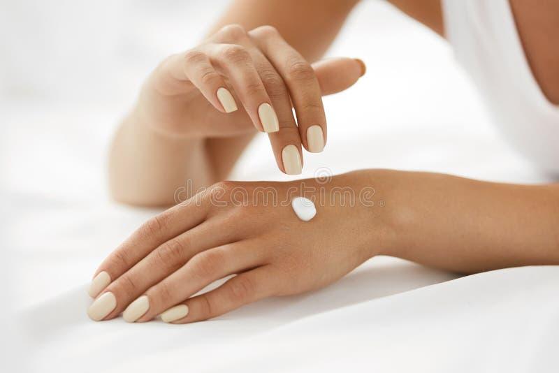Frauenhände mit Sahne Nahaufnahme von den weiblichen Händen, die Lotion anwenden stockbilder