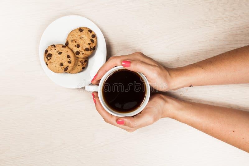 Frauenhände mit Tasse Kaffee mit Plätzchen lizenzfreie stockbilder
