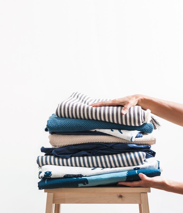 Frauenhände nehmen Stapel der blauen und beige Wäscherei stockfotos