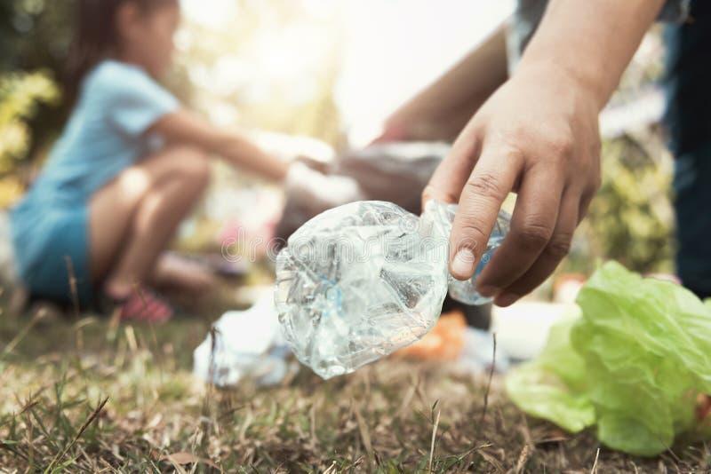 Frauenhand, die Abfallflasche für das Säubern aufhebt lizenzfreie stockbilder