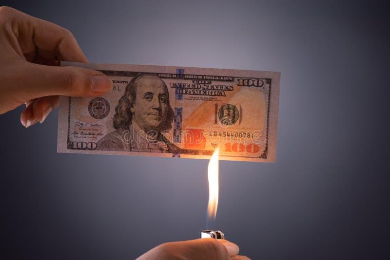Frauenhand, die brennendes brennendes Dollarbargeld ?ber schwarzem Hintergrund - Gesch?ftsfinanzen, Einsparungen und Konkurskonze lizenzfreie stockfotografie