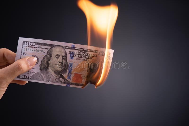 Frauenhand, die brennendes brennendes Dollarbargeld ?ber schwarzem Hintergrund - Gesch?ftsfinanzen, Einsparungen und Konkurskonze lizenzfreies stockfoto