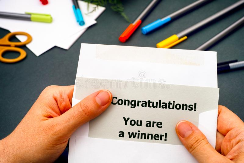Frauenhand, die Brief mit Wörter Glückwünschen herausnimmt! Sie sind ein Sieger! vom Umschlag lizenzfreies stockbild