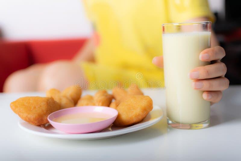 Frauenhand, die das Glas von Sojabohnenmilch auf weißer Tabelle für gesundes Konzept hält lizenzfreies stockfoto