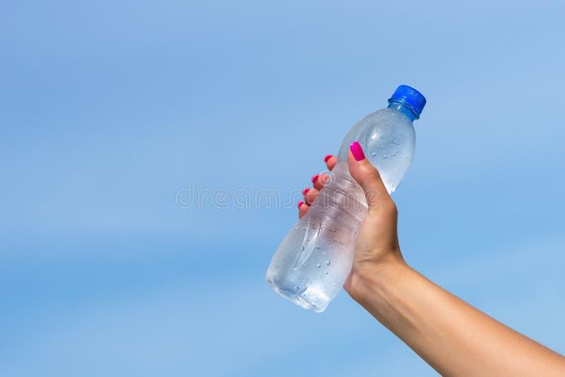 Frauenhand, die draußen Wasserflasche hält lizenzfreies stockbild