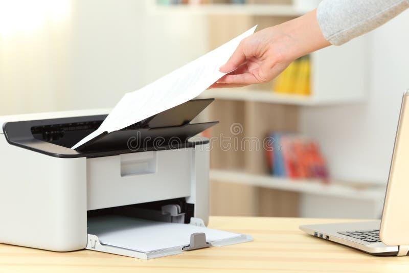 Frauenhand, die ein Dokument von einem Drucker fängt stockbilder