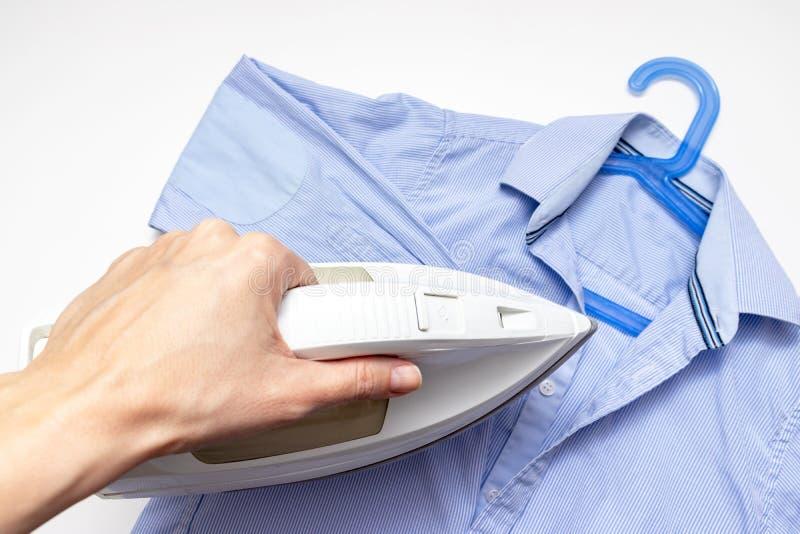 Frauenhand, die ein modernes elektrisches weißes Eisen, ein blaues Hemd auf dem Hintergrund, ein nah herauf Ansicht - Bügeln, Wäs stockbild