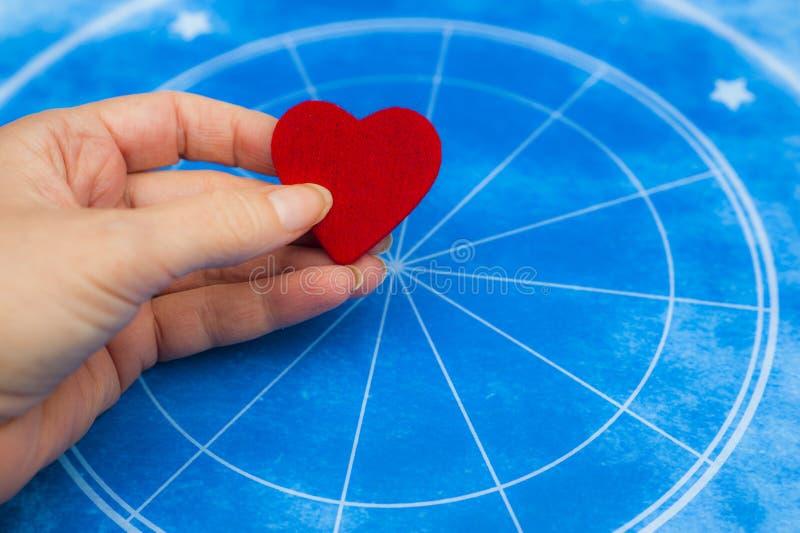 Frauenhand, die ein rotes Herz über blauem Horoskop wie Astrologie-, Tierkreis- und Liebeskonzept hält lizenzfreie stockfotos