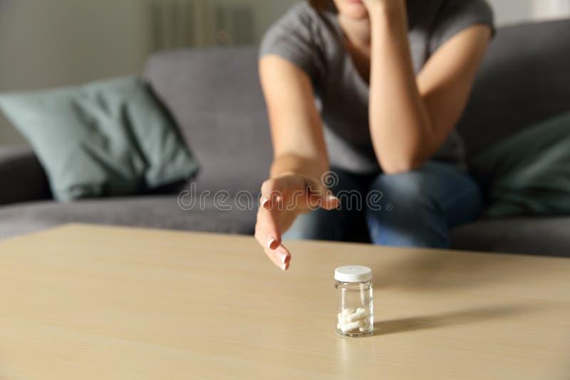 Frauenhand, die eine Flasche Schmerzmittelkapseln erreicht stockbilder