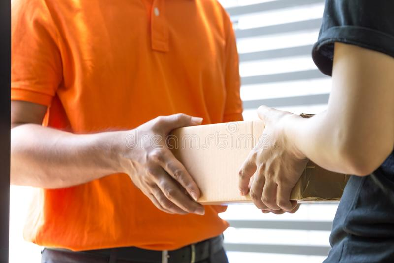 Frauenhand, die eine Lieferung von K?sten vom Lieferboteen annimmt stockfoto