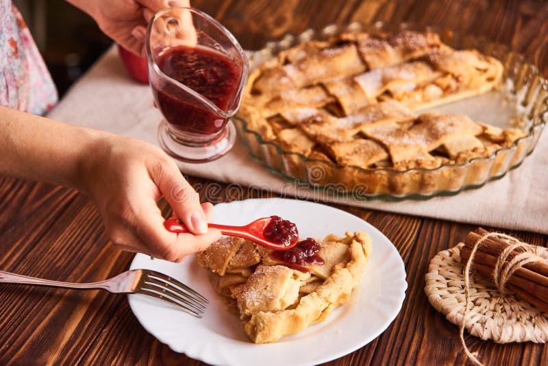 Frauenhand, die einen L?ffel mit einem Stau h?lt Essen des s??en Nahrungsmittelzusammenhangs Traditioneller Feiertagsapfelkuchen  stockbild