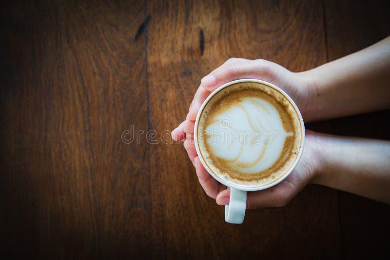 Frauenhand, die einen Tasse Kaffee auf einem alten Holztisch, Draufsicht h?lt stockbilder