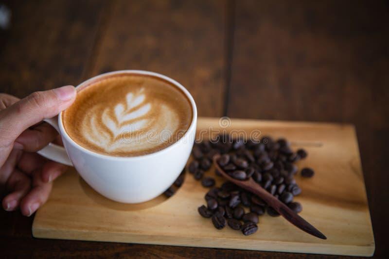 Frauenhand, die einen Tasse Kaffee auf einem alten Holztisch, Draufsicht h?lt lizenzfreies stockbild