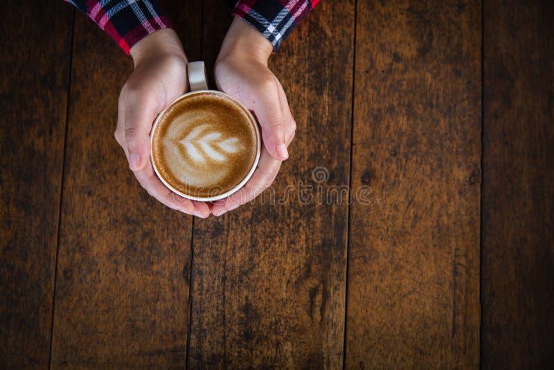 Frauenhand, die einen Tasse Kaffee auf einem alten Holztisch, Draufsicht h?lt stockfotografie