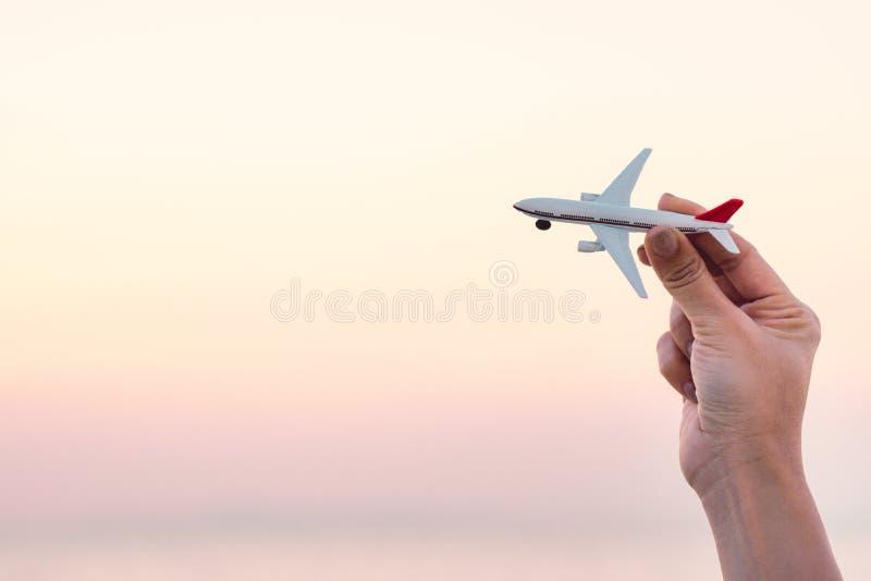 Frauenhand, die Flugzeugmodell in Sonnenunterganghimmel und in Sommermeer b hält lizenzfreie stockfotos