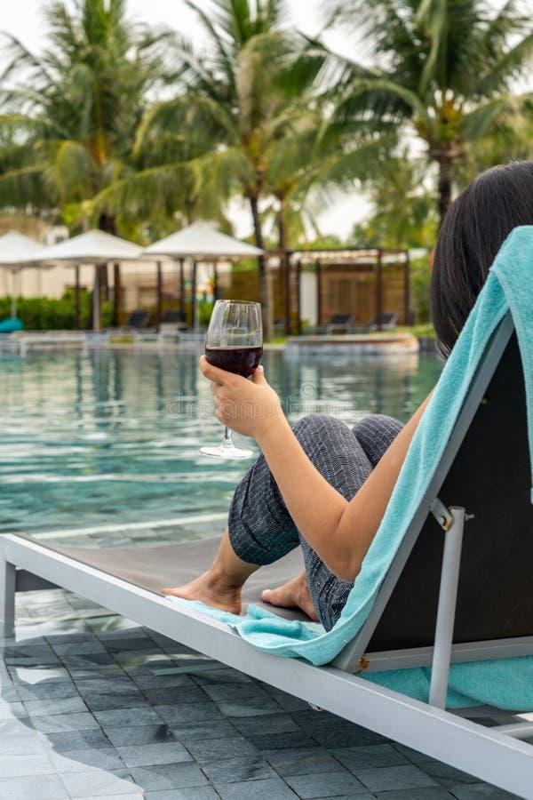 Frauenhand, die Glas Wein am Swimmingpool hält stockbilder