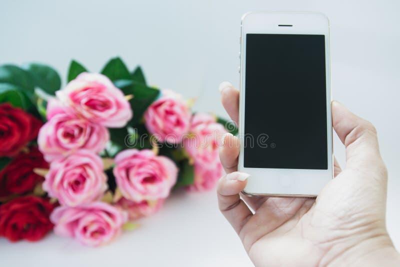 Frauenhand, die Handy mit rosafarbenem Blumenstrauß hält lizenzfreie stockfotos