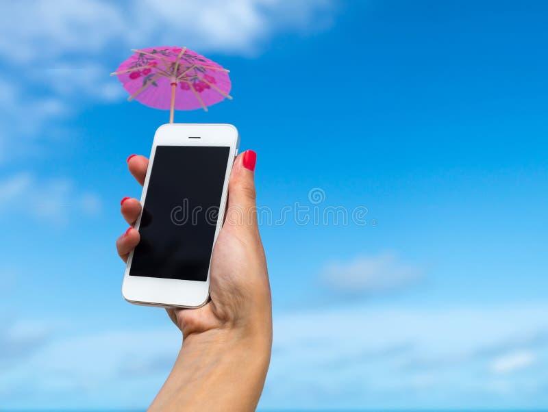 Frauenhand, die Handy- und Cocktailregenschirm auf dem Himmel zeigt stockfoto
