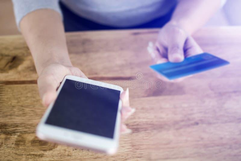 Frauenhand, die Handy und Kreditkarte zum Zahlen des Produktes in der Website online kauft auf dem Holztisch hält lizenzfreies stockbild